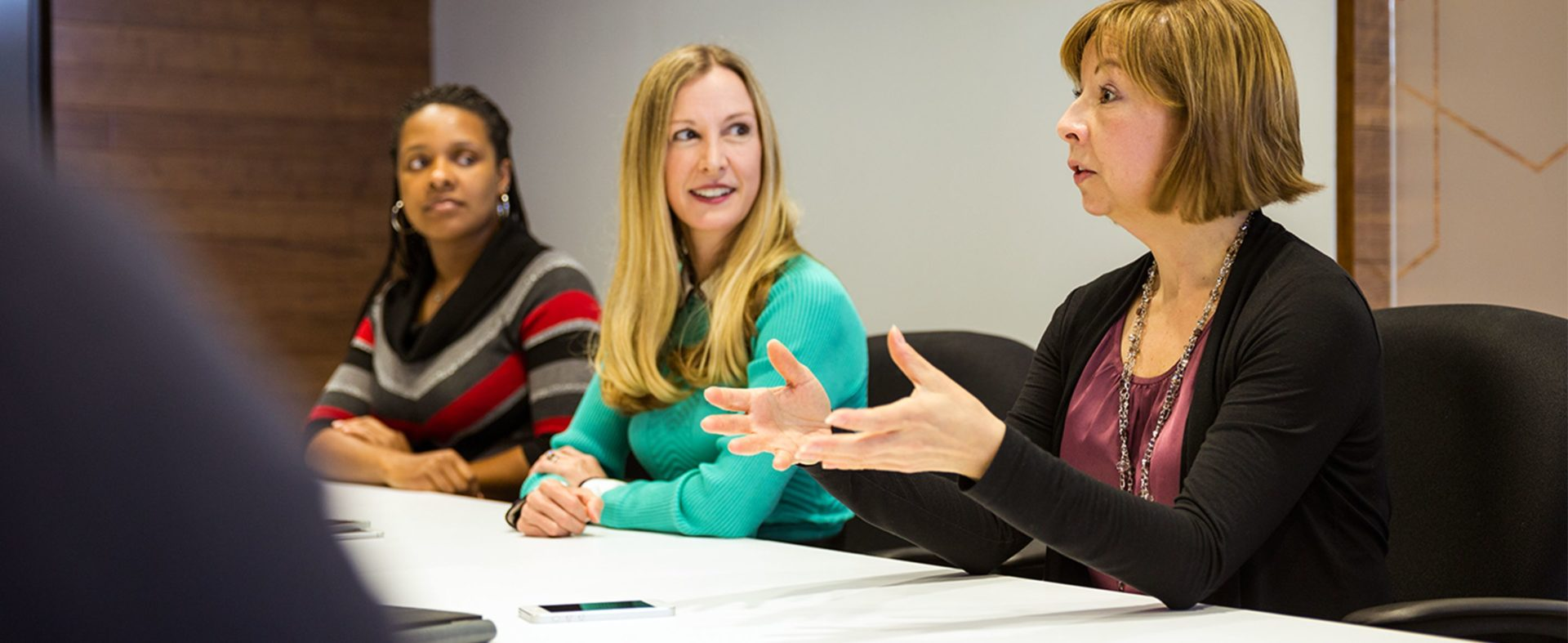 Two women listening to an older woman speaking at a conference table .